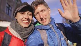 Couples amoureux étreignant, embrassant et faisant le selfie pendant la promenade de ville banque de vidéos
