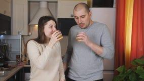 Couples amoureux buvant du jus d'orange dans la cuisine banque de vidéos
