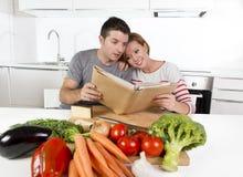 Couples américains fonctionnant dans la cuisine domestique après livre de cuisine de lecture de recette ensemble Photographie stock libre de droits