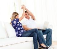 Couples animés jouant avec l'ordinateur portatif se reposant sur le sofa Photo stock