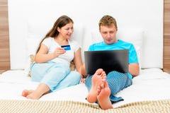 Couples 30 ans achetant les vêtements en ligne Photos stock