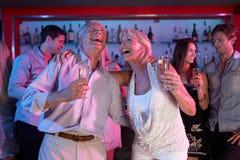 Couples aînés ayant l'amusement dans le bar occupé Image libre de droits