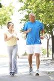 Couples aînés courant en stationnement Images libres de droits