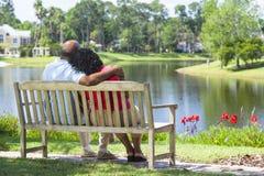 Couples aînés d'Afro-américain sur le banc de stationnement Photo libre de droits