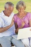 Couples aînés heureux utilisant l'ordinateur portable à l'extérieur Images stock