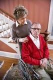Couples aînés à la maison, homme dans le fauteuil roulant Image stock