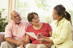 Couples aînés parlant au conseiller financier à la maison Image stock