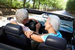 Couples aînés pilotant dans la voiture de sport Photo stock