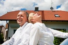 Couples aînés se reposant devant leur maison Photographie stock libre de droits