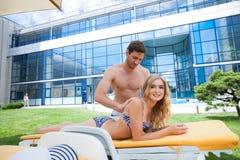 Couples appliquant le sunblock à la plage images libres de droits