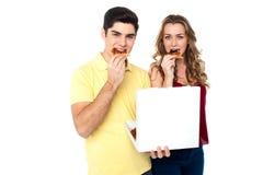 Couples appréciant des tranches de pizza Image stock