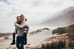 Couples appréciant des vacances d'hiver au bord de la mer Photo stock