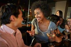 Couples appréciant la boisson à la barre avec des amis Image stock