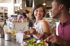 Couples appréciant la date de déjeuner dans le restaurant d'épicerie fine Photo stock