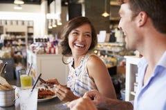 Couples appréciant la date de déjeuner dans le restaurant d'épicerie fine Photos stock