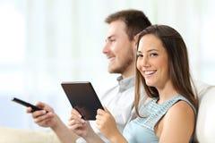 Couples appréciant la TV et vous regardant Photo libre de droits