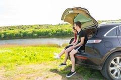 Couples appréciant la vue de la rivière de la porte à rabattement arrière de voiture Image libre de droits