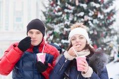 Couples appréciant le cappuccino à un événement de Noël Photo stock