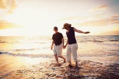Couples appréciant le coucher du soleil à la plage Photographie stock libre de droits