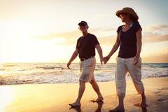 Couples appréciant le coucher du soleil à la plage Images stock
