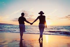 Couples appréciant le coucher du soleil à la plage Images libres de droits