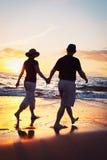 Couples appréciant le coucher du soleil à la plage Photos libres de droits
