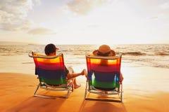 Couples appréciant le coucher du soleil à la plage Image stock