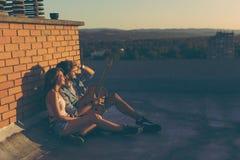 Couples appréciant le coucher du soleil urbain Photographie stock libre de droits