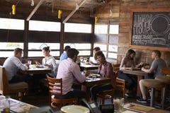 Couples appréciant le déjeuner à un restaurant occupé Images stock