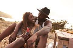 Couples appréciant le pique-nique sur des falaises par la mer Photos stock