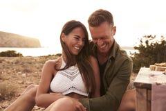 Couples appréciant le pique-nique sur des falaises par la mer Images stock