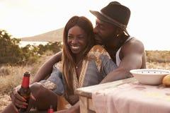 Couples appréciant le pique-nique sur des falaises par la mer Images libres de droits