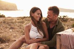 Couples appréciant le pique-nique sur des falaises par la mer Photographie stock