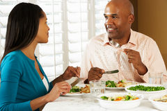 Couples appréciant le repas à la maison Images stock