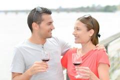 Couples appréciant le vin par la rivière Photos libres de droits