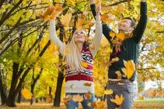 Couples appréciant les feuilles d'automne en baisse en parc Photos libres de droits