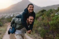 Couples appréciant sur le dos le tour dans la campagne Photographie stock