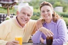 Couples appréciant une boisson par un terrain de golf photographie stock