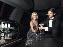 Couples appréciant Champagne In Limousine Photographie stock