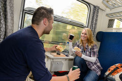 Couples appréciant des sandwichs se déplaçant avec le train Photographie stock