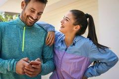 Couples après travail de la position sur la rue, utilisant le téléphone intelligent Photos libres de droits
