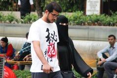 Couples arabes : un jeune homme avec des verres et une barbe marche avec une femme habillée dans un burka noir photo libre de droits