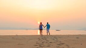 Couples of asian man ,woman happiness on sea beach with sun rising sky stock video