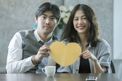 Couples of asian man and woman holding heart shape paper cut wit Royalty Free Stock Image