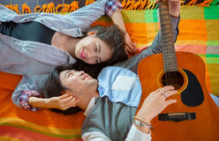 Couples of asian younger man and woman playing guitar with relax Stock Photography