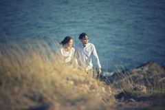 Couples of asian younger man and woman relaxing at sea beach Royalty Free Stock Image