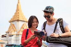 Couples of asian younger traveling man and woman reading message Royalty Free Stock Photo