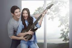 Couples asiatiques attrayants dans l'amour jouant la guitare Photos libres de droits