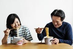 Couples asiatiques ayant la nouille ensemble photographie stock