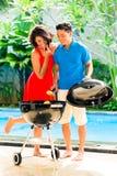 Couples asiatiques ayant le barbecue à la piscine Photo stock